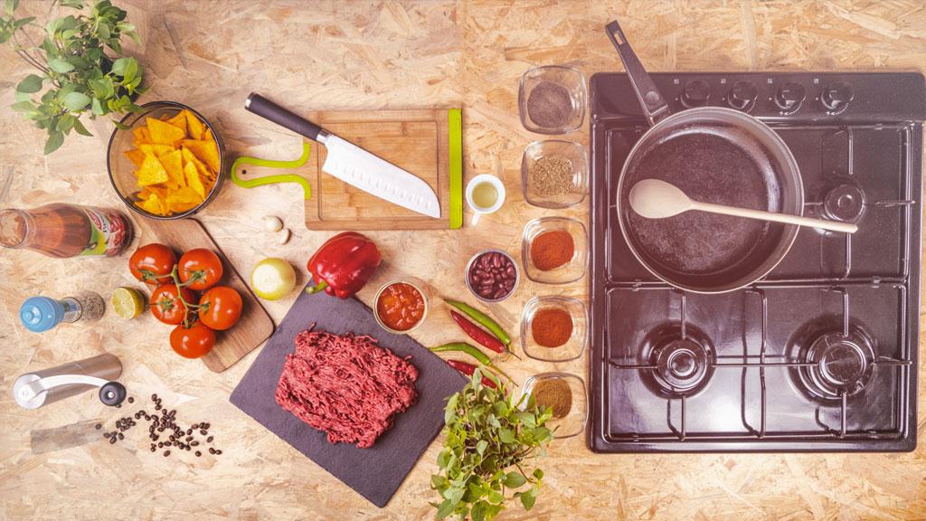 stol-pelen-skladnikow-spozywczych-z-patelnia-i-kuchenka